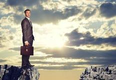 Homem de negócios que está na borda da diferença da rocha Foto de Stock Royalty Free