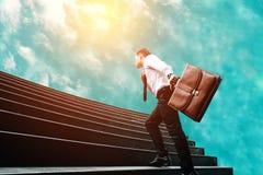 Homem de negócios que está na escada e que move-se para o futuro do céu fotos de stock royalty free