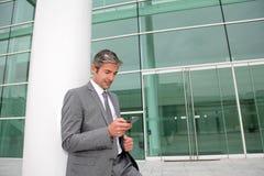 Homem de negócios que está na frente da construção moderna imagens de stock