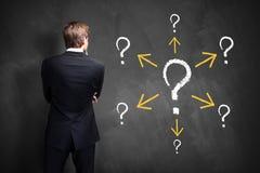 Homem de negócios que está na frente de um quadro-negro com muitos questionmarks Fotos de Stock