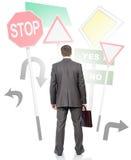 Homem de negócios que está na frente dos sinais de estrada Imagem de Stock