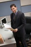 Homem de negócios que está na mesa no compartimento Imagem de Stock Royalty Free