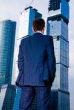 Homem de negócios que está para trás de encontro ao arranha-céus Fotografia de Stock