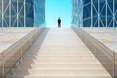 Homem de negócios que está sobre as escadas perto do busine moderno Fotografia de Stock
