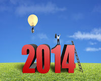Homem de negócios que está sobre 2014, outro no balão da lâmpada Foto de Stock Royalty Free