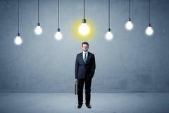Homem de negócios que está uninspired com bulbos acima Foto de Stock