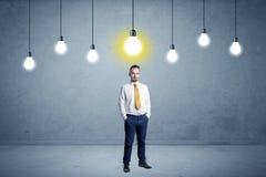 Homem de negócios que está uninspired com bulbos acima Fotografia de Stock Royalty Free