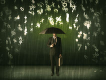 Homem de negócios que estão com guarda-chuva e números 3d que chovem o concep Imagens de Stock
