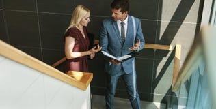 Homem de negócios que fala com o colega fêmea na escadaria do escritório imagens de stock