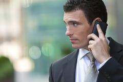 Homem de negócios que fala em seu telefone de pilha Fotografia de Stock