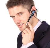 Homem de negócios que fala em uns auriculares Imagens de Stock Royalty Free