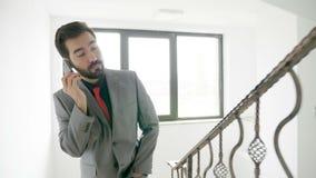 Homem de negócios que fala no telefone ao escalar escadas em um prédio de escritórios vídeos de arquivo