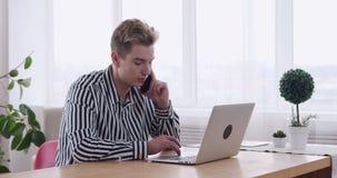 Homem de negócios que fala no telefone celular e que usa o portátil no escritório video estoque