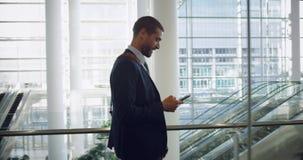 Homem de negócios que fala no telefone celular na entrada no escritório 4k video estoque