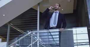 Homem de negócios que fala no telefone celular perto da escadaria no escritório 4k filme