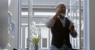 Homem de negócios que fala no telefone celular perto da janela 4k filme