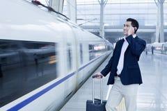 Homem de negócios que fala no telefone na plataforma da estrada de ferro por um trem de alta velocidade no Pequim imagem de stock