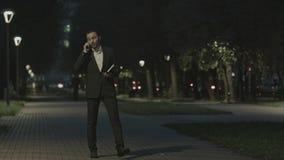 Homem de negócios que fala pelo telefone ao andar no parque e no organizador do uso fotos de stock