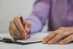 Homem de negócios que faz anotações no papel em seu escritório Fotografia de Stock Royalty Free
