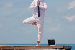 Homem de negócios que faz a ioga em uma ponte de madeira com um portátil Fotos de Stock