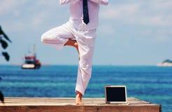 Homem de negócios que faz a ioga em uma ponte de madeira com um portátil Fotografia de Stock
