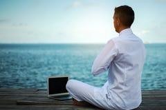 Homem de negócios que faz a ioga em uma ponte de madeira com um portátil Fotos de Stock Royalty Free