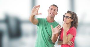 Homem de negócios que faz o quadro da mão pela mulher no escritório imagem de stock royalty free