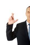 Homem de negócios que faz um desejo com os dedos cruzados Foto de Stock Royalty Free