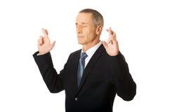 Homem de negócios que faz um desejo com os dedos cruzados Fotos de Stock Royalty Free