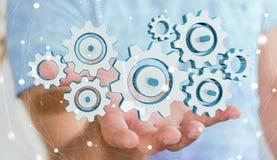 Homem de negócios que guarda ícones coloridos da engrenagem em sua rendição da mão 3D Foto de Stock Royalty Free