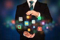 Homem de negócios que guarda ícones da aplicação Imagens de Stock