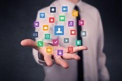 Homem de negócios que guarda aplicações coloridas Foto de Stock
