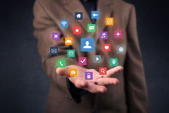 Homem de negócios que guarda aplicações coloridas Imagens de Stock