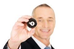 Homem de negócios que guarda a bola de bilhar preta Fotografia de Stock Royalty Free
