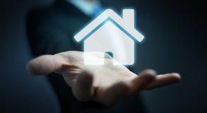 Homem de negócios que guarda a casa do ícone da rendição 3D em sua mão Imagens de Stock