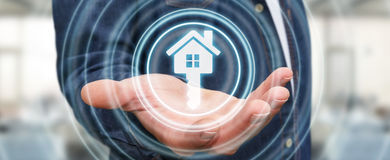 Homem de negócios que guarda a casa do ícone da rendição 3D em sua mão Foto de Stock