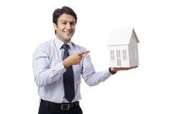 Homem de negócios que guarda a casa modelo Fotos de Stock