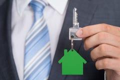 Homem de negócios que guarda chave com keychain da casa verde Fotografia de Stock Royalty Free