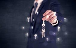 Homem de negócios que guarda chaves com chaves ao redor Imagem de Stock
