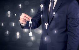 Homem de negócios que guarda chaves com chaves ao redor Fotos de Stock