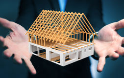 Homem de negócios que guarda 3D que rende a casa inacabado do plano em seu ha Imagem de Stock Royalty Free