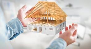 Homem de negócios que guarda 3D que rende a casa inacabado do plano em seu ha Imagem de Stock