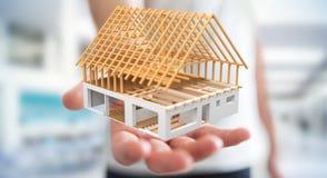 Homem de negócios que guarda 3D que rende a casa inacabado do plano em seu ha Foto de Stock Royalty Free