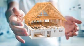 Homem de negócios que guarda 3D que rende a casa inacabado do plano em seu ha Imagens de Stock Royalty Free