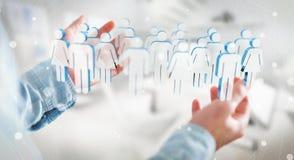 Homem de negócios que guarda 3D que rende o grupo de pessoas em sua mão Imagens de Stock Royalty Free