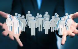 Homem de negócios que guarda 3D que rende o grupo de pessoas em sua mão Foto de Stock Royalty Free