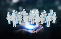 Homem de negócios que guarda 3D que rende o grupo de pessoas em sua mão Imagens de Stock