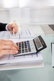 Homem de negócios que guarda despesa calculadora no escritório Imagens de Stock