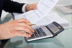 Homem de negócios que guarda despesa calculadora no escritório Imagem de Stock