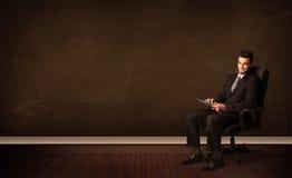 Homem de negócios que guarda a elevação - tabuleta da tecnologia no fundo com copyspac Fotografia de Stock